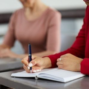 Mid section closeup of mixed-race businesswoman taking notes in class during management training, copy